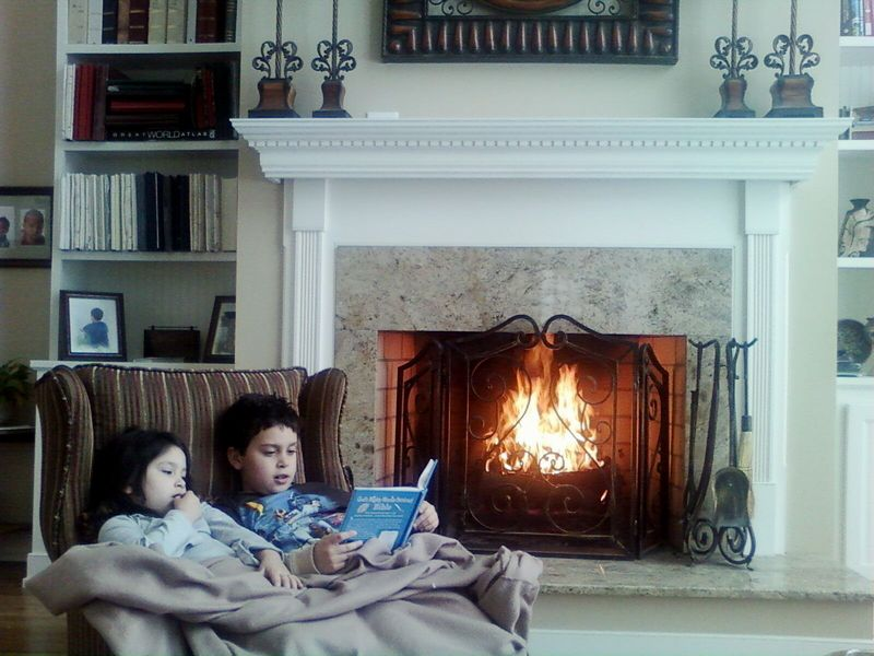 Kids reading by fire
