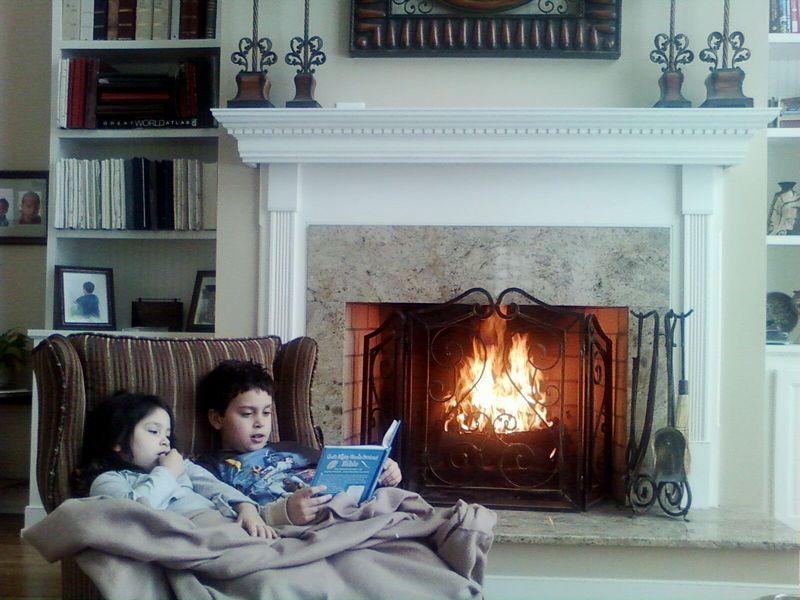 Kids reading by fire